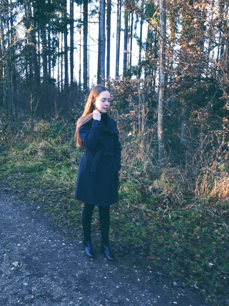 Ein blondes Mädchen in einem grauen Mantel steht auf einem Weg im Wald. Man sieht sie von schräg vorne. Ihre Haare werden von der untergehenden Sonne beleuchtet. Sie schaut verträumt nach schräg unten.