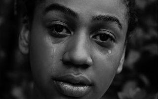 Eine Frau schaut mit starkem Blick in die Kamera, während ihr Tränen über die Wangen laufen