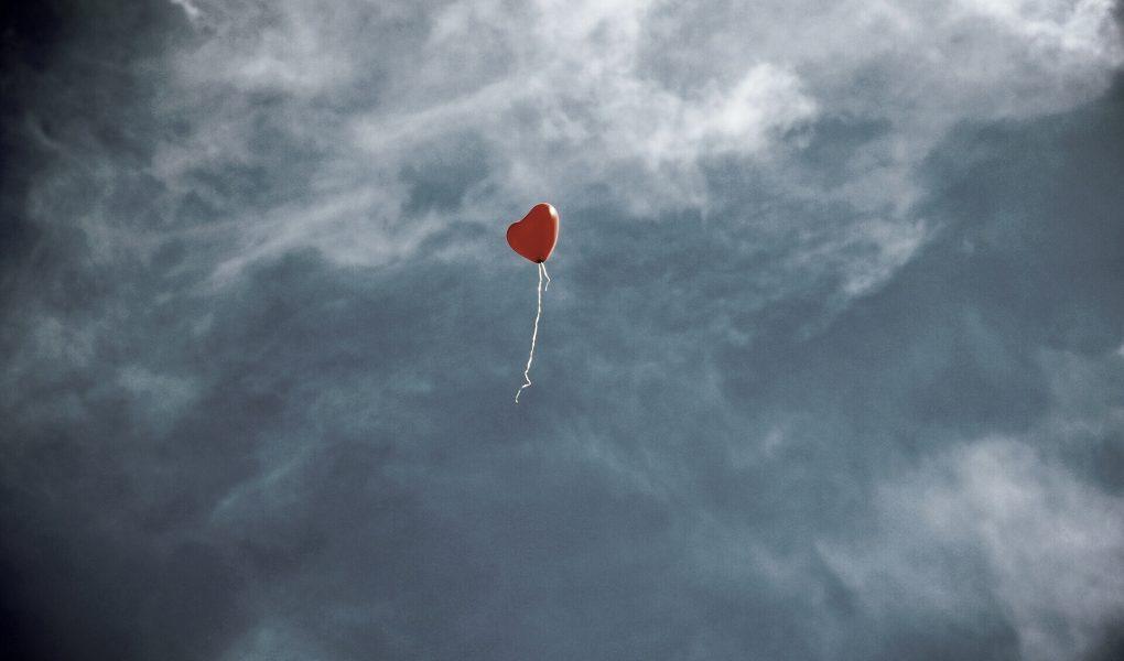 Ein herzförmiger, roter Ballon flieg in den Himmel. Alles ist in sehr gedeckten Farben gehalten
