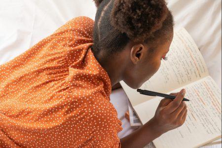 Ein Mädchen mit dunklen, lockigen Haaren liegt auf dem Bett. Um sie herum befinden sich mehrere aufgeschlagene Bücher. In eines davon schreibt sie konzentriert. Das Bild ist von schräg oben aufgenommen.