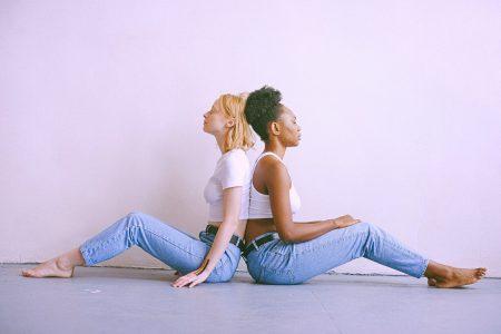 Zwei Frauen sitzen Rücken an Rücken vor einer hellen Wand. Sie tragen jeweils Jeans und ein weißes Top