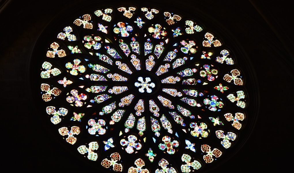 Ein rundes Buntglasfenster. Es sieht aus wie ein Mandala aus verschiedenen, kleinteiligen Formen bestehend aus buntem Glas