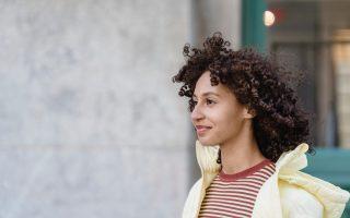 Eine Frau mit dunklen, sehr lockigen Haaren läuft lächelnd die Straße entlang. Man sieht nur Kopf und Oberkörper. Sie trägt ein rot-weiß gestreiftes T-Shirt und eine gelbe Steppjacke