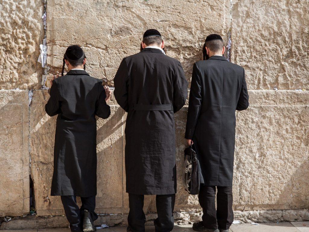 Drei Männer in der jüdischen religiösen Kleidung stehen betend an der Klagemauer