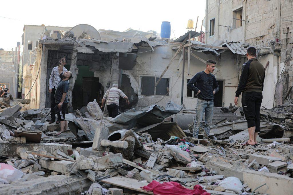 Man sieht 5 Männer, die auf einem mit Schutt bedecktem Boden stehen. Überall liegen Trümmer herum, im Hintergrund steht ein halb zusammengefallenes Haus. Vemutlich gehören die Schutteile auch zu einem Wohnhaus und die Männer betrachten die Schäden.