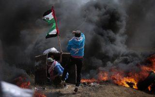 Man sieht den Rücken zweier Männer, die auf einer Erhöhung stehen und auf Feuer und eine dicke Rauchwolke vor ihnen schauen. Sie tragen Straßenkleidung obwohl sie anschenend kämpfen. Der Eine schießt mit einer Steinschleuder. Neben ihnen ist eine zerfetzte palästinensische Flagge